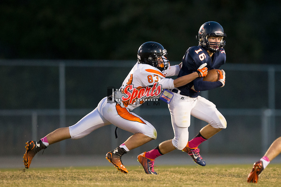 Cameron Rayfield (16) of the Carson Cougars is hit by Tyler Ervin (83) at Jesse Carson High School on October 24, 2014, in China Grove, North Carolina.  The Cougars defeated the Trojans 35-6.  (Brian Westerholt/Sports On Film)