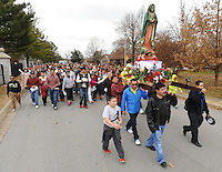 NWA Media/ANDY SHUPE - Parishioners lead a large crowd while walking with an Our Lady of Guadalupe stature during the ninth-annual pilgrimage walk to celebrate The Feast of Our Lady of Guadalupe Sunday, Dec. 14, 2014, in Fayetteville. Worshipers walked from St. Joseph Catholic Church in Fayetteville to St. Raphael Church in Springdale. Visit nwamedia.photoshelter.com to see more photos from the event.