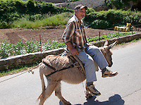 Man riding a donkey through Dol, Bra? island, Croatia