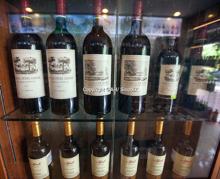 1.5 litre bottles of Baron de Rothschild (L) and Lafite (M) wine of indeterminate authenticity are seen in a shop that sells real and fake wine, Guangzhou, Guangdong Province, China, 18 July 2014. <br /> <br /> PHOTO BY SINOPIX