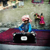 A young boy practices the harmonium in the Kathputli Colony. Located in northwest Delhi, Kathputli is inhabited by approximately 2,000 performing artists, practicing traditional art forms such as marionette puppetry, juggling, magic, acrobatics, dance and music. Many have travelled all over the world showcasing their abilities, but they still choose to remain living in this slum, which is one of the most impoverished in the city.