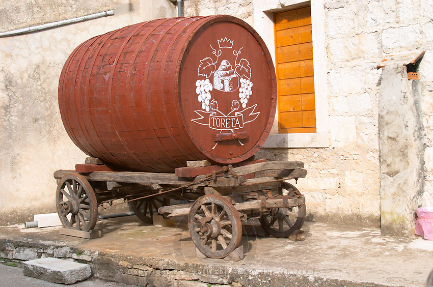 An old wooden cart with a big barrel for transporting wine used as a promotional sign outside the winery. Toreta Vinarija Winery in Smokvica village on Korcula island. Vinarija Toreta Winery, Smokvica town. Vinarija Toreta Winery, Smokvica town. Peljesac peninsula. Dalmatian Coast, Croatia, Europe.