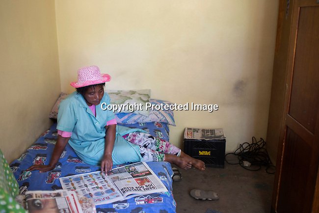 CAPE TOWN, SOUTH AFRICA - NOVEMBER 19: Cornelia Klaase a farmworker at a wine farm, reads a newspaper in her bedroom on November 19, 2015 in in Boland area outside of Cape Town, South Africa  (Photo by: Per-Anders Pettersson)