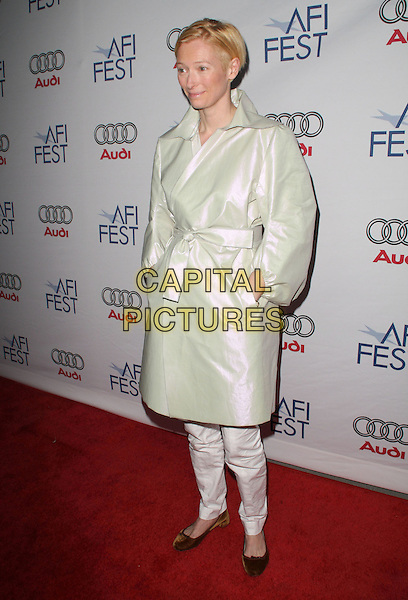 TILDA SWINTON.AFI Tribute to Tilda Swinton held at the Arclight Theatre, Hollywood, California, USA..November 5th, 2008.full length white trousers gold cream mac trenchcoat hands in pockets .CAP/ADM/KB.©Kevan Brooks/AdMedia/Capital Pictures.