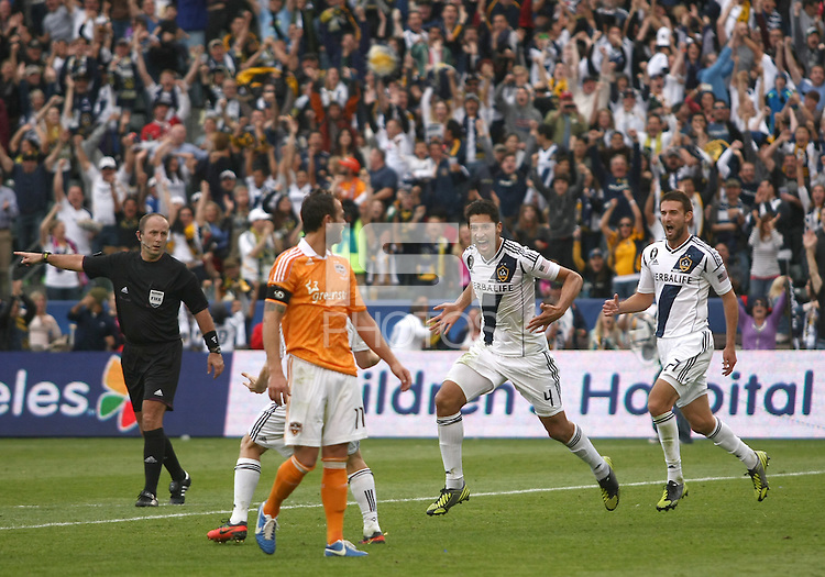 CARSON, CA - DECEMBER 01, 2012:   Omar Gonzalez (4) of the Los Angeles Galaxy runs towards Brad Davis (11) of the Houston Dynamo after scoring during the 2012 MLS Cup at the Home Depot Center, in Carson, California on December 01, 2012. The Galaxy won 3-1.