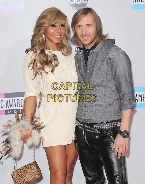 Cathy Guetta & David Guetta.2011 American Music Awards - Arrivals held at Nokia Theatre LA Live, Los Angeles, California, USA..November 20th, 2011.ama amas ama's half length.white cream fringed dress black leather trousers grey gray jacket beard facial hair married husband wife.CAP/RKE/DVS .©DVS/RockinExposures/Capital Pictures.