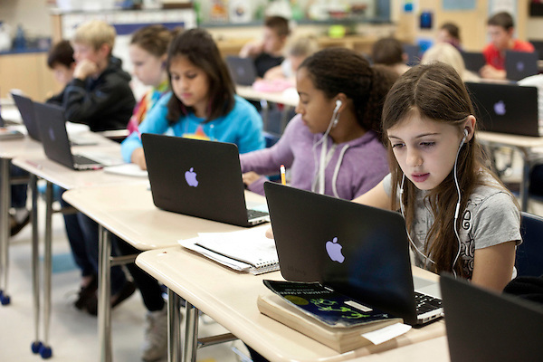 November 15, 2011. Mooresville, NC.. Caitlyn Yaede, age 10, right,  works on a 5th grade science lesson at East Mooresville Intermediate School. Many of the in-class lessons are done on school issued laptops and turned in to the teacher via networked printer.. The Mooresville school system has become nationally known for being on the cutting edge of using technology as an educational tool. Starting in 3rd grade, each student is issued their own laptop that they will use in class and at home to further their learning.