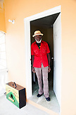 "JAMAICA, Port Antonio. Derrick ""Johnny"" Henry of the Mento band, The Jolly Boys, standing in the front door of his house."
