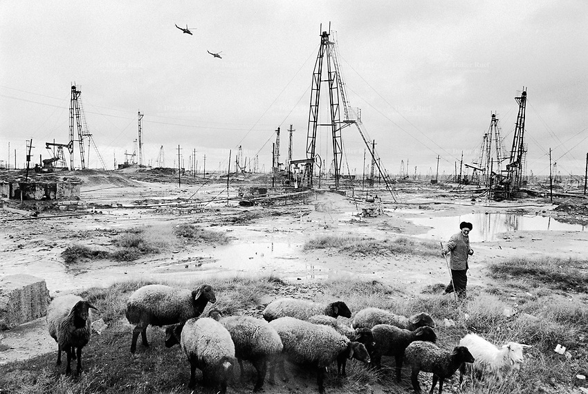 Azerbaijan. Baku Region. Baku. A shepherd and his flock of sheeps. Two flying helicopters gunships from the Azerbaijan army in the cloudy sky. State Oil Company of Azerbaijan Republic (SOCAR) is the project owner of the oil fields in Balakhani. Oil-extracting infrastructure. Wells heads and nodding donkeys. Drilling derricks and rigs. Spill and oil leakage from installation in operation. Oil production. Ecological disaster. Balakhani Oil Fields are a source of pollution as a result of well water and oil spill discharge. Oil well. © 2007 Didier Ruef