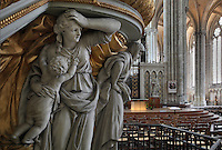 Statues supporting the pulpit representing Faith, Hope and Charity, carved in wood then painted and gilded in 1773, designed by Pierre-Joseph Christophle, 1715-1782, on the north side of the nave in the Basilique Cathedrale Notre-Dame d'Amiens or Cathedral Basilica of Our Lady of Amiens, built 1220-70 in Gothic style, Amiens, Picardy, France. Behind is the rood screen and entrance to the choir. Amiens Cathedral was listed as a UNESCO World Heritage Site in 1981. Picture by Manuel Cohen