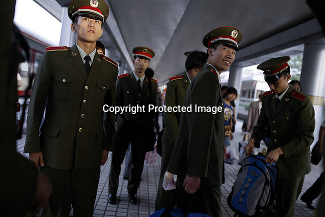 Chinese soldiers walk off a train early in the morning as a night train from Xian - Lanzhou have just arrived. The train traveled for about 9 hours to Lanzhou. Train travel in China is cheap and reliable, and it is the most popular way of transport for Chinese people. (Photo by: Per-Anders Pettersson)