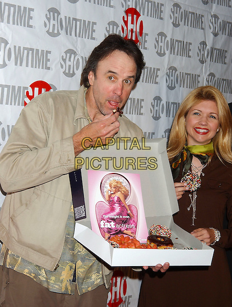 KEVIN NEALON & SUSAN YEAGLEY.Fat Actress Los Angeles Premiere held at the Cinerama Dome at Arclight Cinemas. Hollywood, California.Photo Credit: Laura Farr/AdMedia.February 23rd, 2005.half length funny doughnut food eating gesture donut.www.capitalpictures.com.sales@capitalpictures.com.© Capital Pictures.