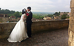 A just-married couple take advantage of a moment while waiting for their photographer in the French village of Ste. Emilion.