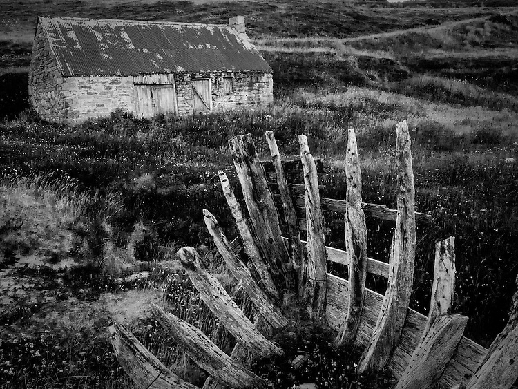Old farm building on moorland with derelict boat timbers