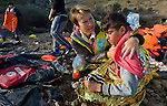 A volunteer from Norway hugs a refugee boy she has wrapped in an emergency blanket on a beach near Molyvos, on the Greek island of Lesbos, on October 30, 2015. The refugees were on a boat that traveled to Lesbos from Turkey, provided by Turkish traffickers to whom the refugees paid huge sums. Hundreds of foreign and local volunteers on the island receive the refugees and provide them with warm clothing, food and medical care before they continue their journey toward western Europe.