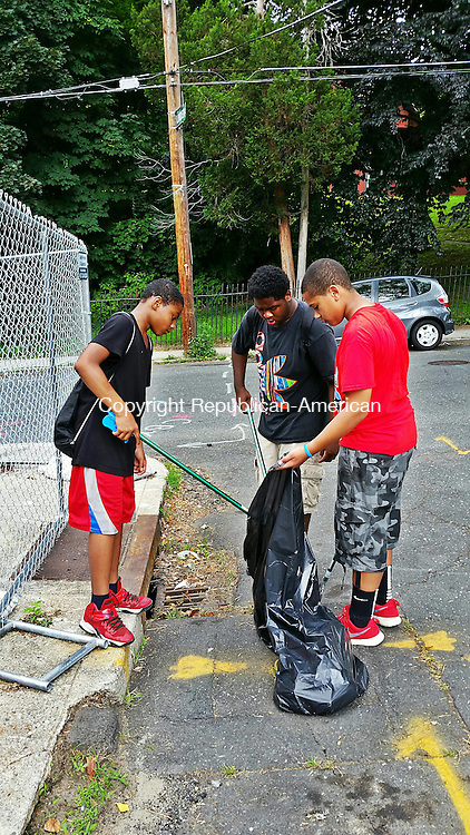 WATERBURY -- July 8, 2015 -- 07_NEW_070815MDP02 -- Three children from the Connecticut Junior Republic state program for troubled youths clean up Prospect Street downtown on Tuesday. Left to right are Jeremiah Tripp, 12, Emory Slade, 15, and Christian Jimenez, 13.