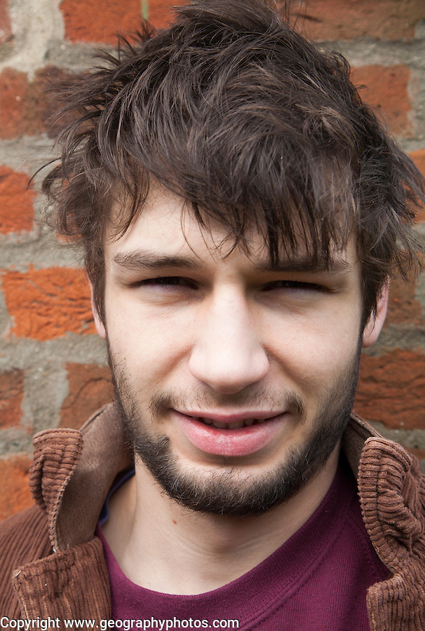 Model released close up portrait of 20 year old man with beard, UK