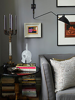 Neat piles of books occupy the floor space beneath an Empire occasional table beside the sofa in this small living room