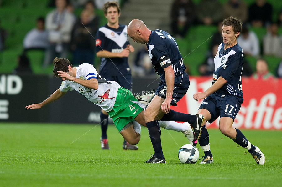 MELBOURNE, AUSTRALIA - May 14, 2010: Michael Zullo from the Come Play XI falls to the ground as Kevin Muscat from Melbourne Victory controls the ball at the Kevin Muscat Testimonial match between the Melbourne Victory and Come Play XI at AAMI Park on May 14, 2010 in Melbourne, Australia. Photo Sydney Low www.syd-low.com