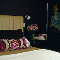 Dark colours have been used in the bedroom with a contrasting light padded headboard against a dark blue wall