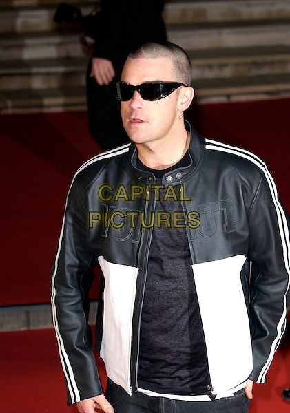 ROBBIE WILLIAMS.Brit Awards 2005.Earls Court 2, London, SW5.February 10th, 2005.half length shaved head sunglasses shades black and white leather jacket.www.capitalpictures.com.sales@capitalpictures.com.©Capital Pictures