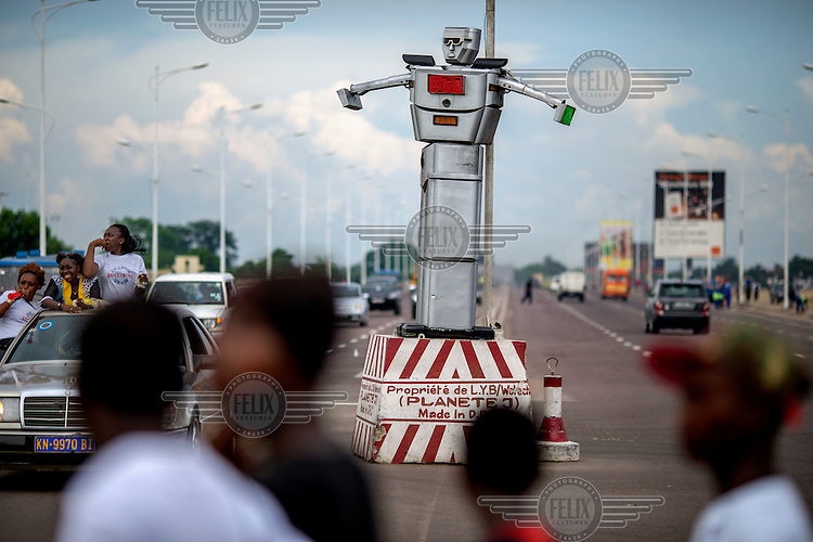 An 8 foot tall, solar powered humanoid traffic robot equipped with a rotating chest and video cameras controls and monitors traffic on a busy road in Kinshasa.
