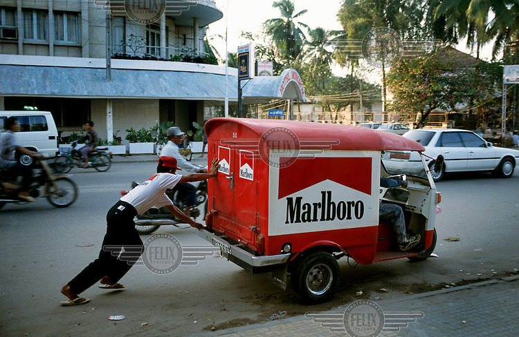 A broken down van distributing Marlboro cigarettes is pushed along a city street.