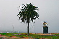 Statue of Bolivar El Libertador, The Liberator, sitting on a horse on a black marble pedestal. with a palm tree and the horizon., on the riverside seaside walk along the river Rio de la Plata Ramblas Sur, Gran Bretagna and Republica Argentina Montevideo, Uruguay, South America
