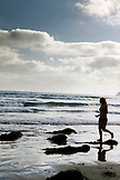 USA, California, San Diego, USA, California, San Diego, girl runs toward the waves in front of Hotel Del Coronado