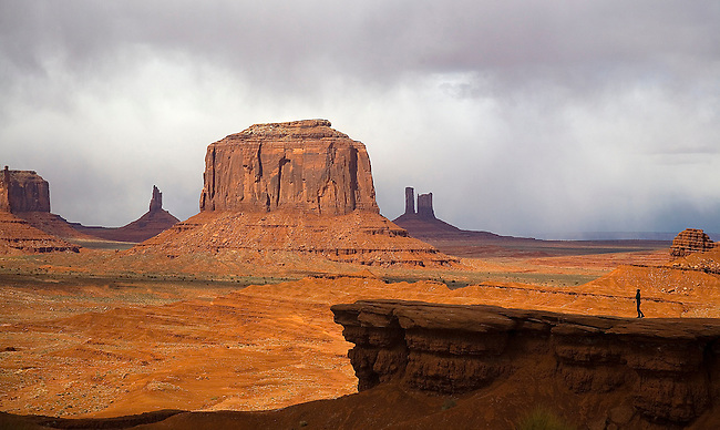 A LONE TOURIST IS SILHOUETTED AGAINST THE BACKDROP OF MONUMENT VALLEY IN ARIZONA