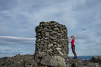 Female hiker stands next to large summit cairn on Matmora mountain peak, Austvågøy, Lofoten Islands, Norway