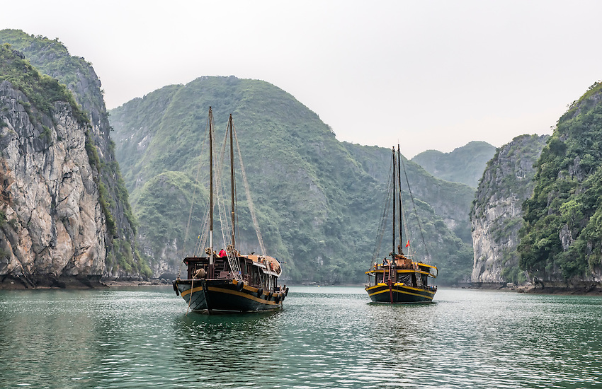 """Boats sit moored in Ha Long Bay, Vietnam. Ha Long Bay, located on the east coast of Vietnam near Haiphong, contains over 1,900 limestone """"karst"""" islands projecting from the sea. They are frequently shrouded in fog, mist and rain, as seen in these photos."""