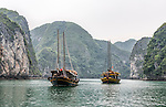 "Boats sit moored in Ha Long Bay, Vietnam. Ha Long Bay, located on the east coast of Vietnam near Haiphong, contains over 1,900 limestone ""karst"" islands projecting from the sea. They are frequently shrouded in fog, mist and rain, as seen in these photos."
