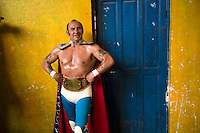 Wrestler Mister Atlas stands in his costume outside the changing room at the Multifuncional building where every Sunday wrestling takes place.