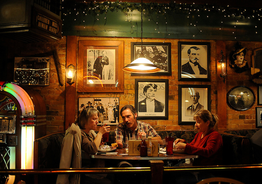 From the left, Brenda Moen, of Whitefish, MT, Paul and Gail Schoeppner of Silt, CO, enjoy a meal at the Doc Holliday Tavern. Historic photographs line the walls. Michael Brands for The New York Times.