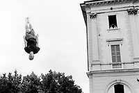 Switzerland. Canton Ticino. Lugano. A young man enjoys trampoline and flies in the air in front of the Town Hall building. A man and a woman, both working for the police force, look at the show from a window. © 1992 Didier Ruef