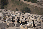 Orthodox Jewish men walk past an Israeli soldier, at the old cemetery on Mt. Olives in Jerusalem, Israel, during 'Yom Hazikaron' Memorial Day ('Israeli Fallen Soldiers and Victims of Terrorism Remembrance Day').