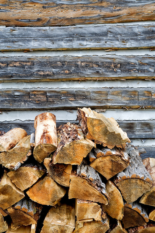 Cord wood stacked next to old log cabin. Nevada City, Montana