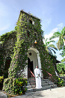 Priest greeting Sunday church worshippers at Ivy covered church in St. Ann's Bay, Jamaica. Jamaica Tourism.