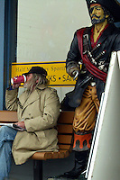 "Outside a fishing supply shop a local enjoys his morning paper and cup of coffee while ""Captain Hook"" keeps an eye on the parking lot and Pillar Point Harbor."