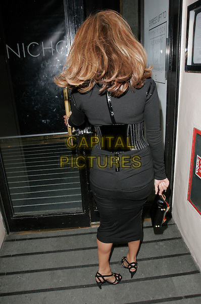EVA MENDES.Attends Mulberry For Giles Bags - Launch Party at Harvey Nichols, Knightsbridge, London, England, .January 30th 2007..full length black top polo neck waist belt patent pencil skirt strappy shoes sandals back behind rear hair opening door.CAP/AH.©Adam Houghton/Capital Pictures.