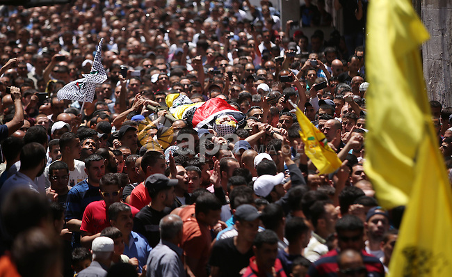 Palestinians carry the body of Mohammad Kasbeh during his funeral in Qalandia near the West Bank city of Ramallah, July 3, 2015. Israeli military's soldiers fatally shot a 17-year-old Palestinian near Qalandiya refugee camp close to Ramallah. The youth, who has been identified as Mohammad Kasbeh, was throwing stones at an army patrol, according to the Israeli military. Palestinian sources dispute this version of events. Photo by Shadi Hatem