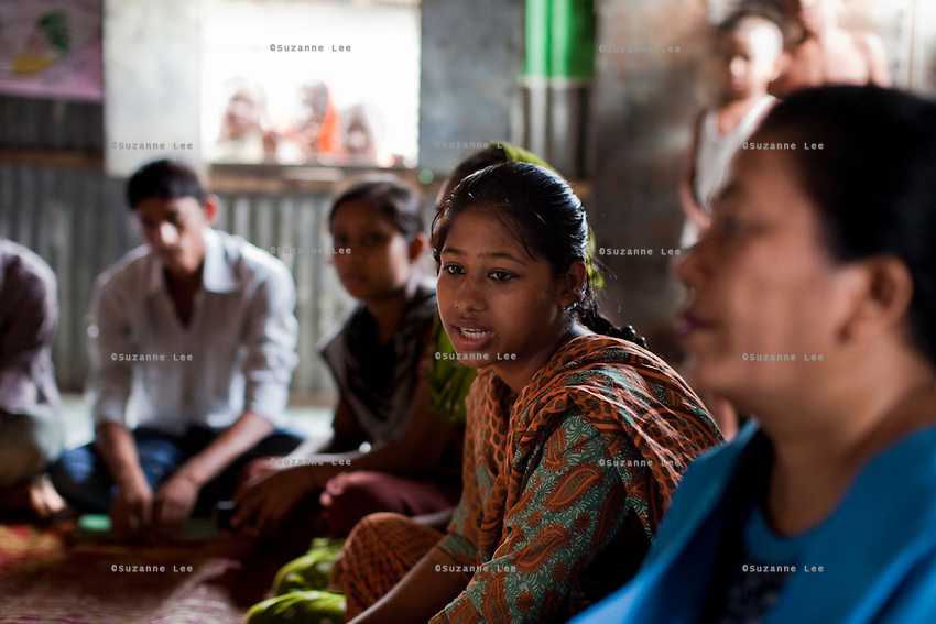 "Nusrat Jahan Popy (16, 2nd from right) speaks during a monthly meeting of a Children's Group in Bhashantek Basti (Slum) in Zon H, Dhaka, Bangladesh on 23rd September 2011. Popy says, ""I feel helpless, not angry (if my parents would try to marry me off). I can do stitching and we want to be allowed to work so that we can earn money to support ourselves in our studies and to rid ourselves of poverty and gain independence."" The Bhashantek Basti Childrens Group is run by children for children with the facilitation of PLAN Bangladesh and other partner NGOs. Slum children from ages 8 to 17 run the group within their own communities to protect vulnerable children from child related issues such as child marriage. Photo by Suzanne Lee for The Guardian"