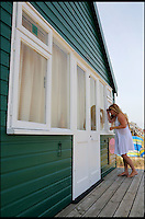 BNPS.co.uk (01202 558833)<br /> Pic: CorinMesser/BournemouthEcho/BNPS<br /> <br /> A passer-by sneaking a peek into the beach hut. <br /> <br /> Britain's most expensive beach hut has gone on the market for a whopping 225,000 pounds - and it doesn't even come with sea views.<br /> <br /> The wooden shack, that measures 13ft by 13ft, looks out onto sand dunes and offers  glimpses of the sea. It is also right next to a public toilet block.<br /> <br /> The timber hut on Mudeford Spit near Christchurch, Dorset, is divided up into three rooms - a living area, bedroom and a mezzanine level.<br /> <br /> It has no bathroom, mains electricity or running water and requires a ride on a novelty land train or a 30 minute walk to get there.