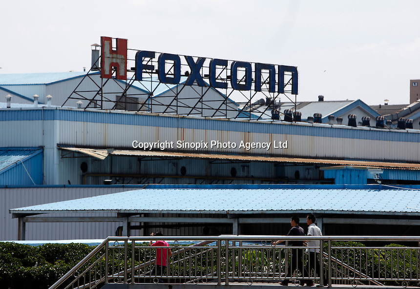 Workers walk outside Hon Hai Group's Foxconn plant in Shenzhen, China. Hon Hai is the parts supplier for many hi-tech companies around the world including Apple Inc., Hewlett-Packard Co. and Dell Inc. There have been 12 suicides at the company's 300 thousand employee strong factory complex in Shenzhen so far this year..26 May 2010
