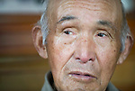 Minoru Oka, 85, speaks at his home in Minamisoma, Fukushima Prefecture, Japan on Friday 05 August, 2011.  For Oka the nuclear crisis that began almost 5 months ago just down the road from his home  following the March 11 quake and tsunami is his second brush with the threat of radiation. .When the atomic bomb was dropped on Hiroshima on Aug. 6, 1945, Oka was a 19-year-old member of an Imperial Japanese Army unit located in Hiroshima..Photographer: Robert Gilhooly