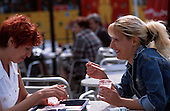 Bucharest, Romania. Two women eating icecream; packet of cigarettes on the table.