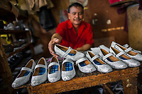 A Salvadoran shoemaker displays newly made pairs of girl's silver glitter shoes on the workbench in a shoe making workshop in San Salvador, El Salvador, 16 November 2016.