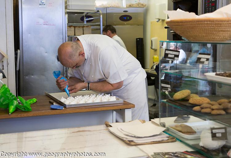 Expert baker craftsman making meringues inside the Little Bakehouse bakery shop, Devizes, Wiltshire, England, UK