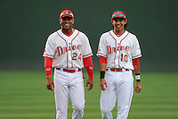 Second baseman Yoan Moncada (24) of the Greenville Drive, left, walks with Mauricio Dubon (10) before a game against the Lexington Legends on Monday, May 18, 2015, at Fluor Field at the West End in Greenville, South Carolina. Moncada, a 19-year-old prospect from Cuba, made his professional debut tonight in the Red Sox organization. (Tom Priddy/Four Seam Images)